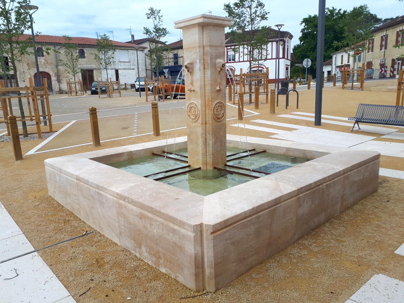 La fontaine et derrière, la place et le village